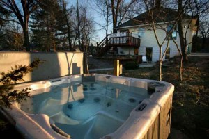 backyard hottub surrounded by trees at sunset